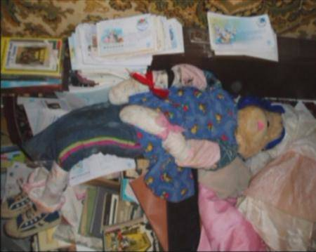 A still image taken from undated police footage shot inside the flat of Anatoly Moskvin shows books, clothes and dressed figures, reportedly mummified bodies desecrated from cemeteries