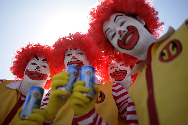 Men dressed as Ronald McDonald pose with cans of beer during the Race of Beer in Brasilia