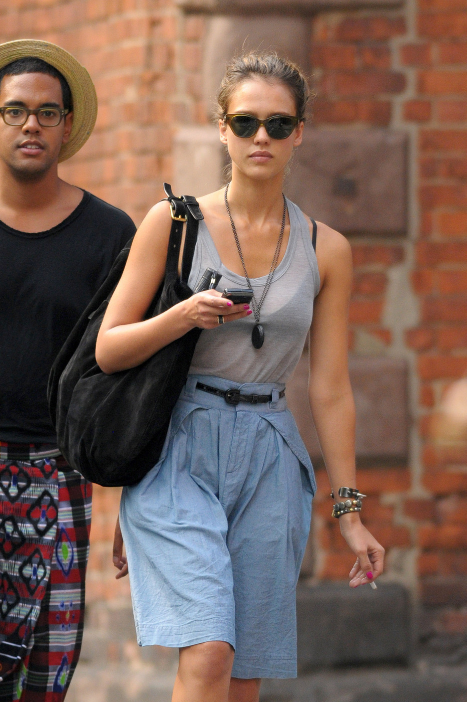 CELEB SMOKERS: Jessica Alba holds a cell phone in one hand a cigarette in the other while out shopping with a friend in Soho