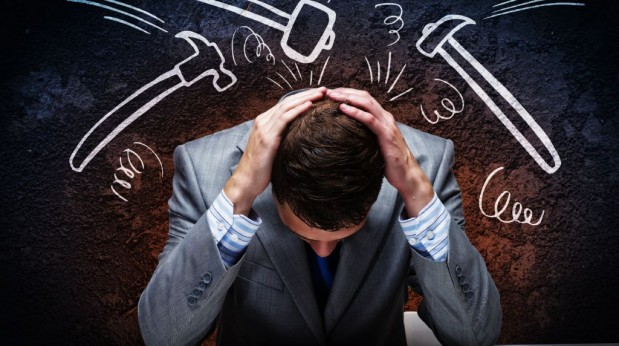 Hombre-con-traje-fracasado-con-la-cabeza-agachada-y-varios-martillos-dibujados-sobre-su-cabeza-619x346