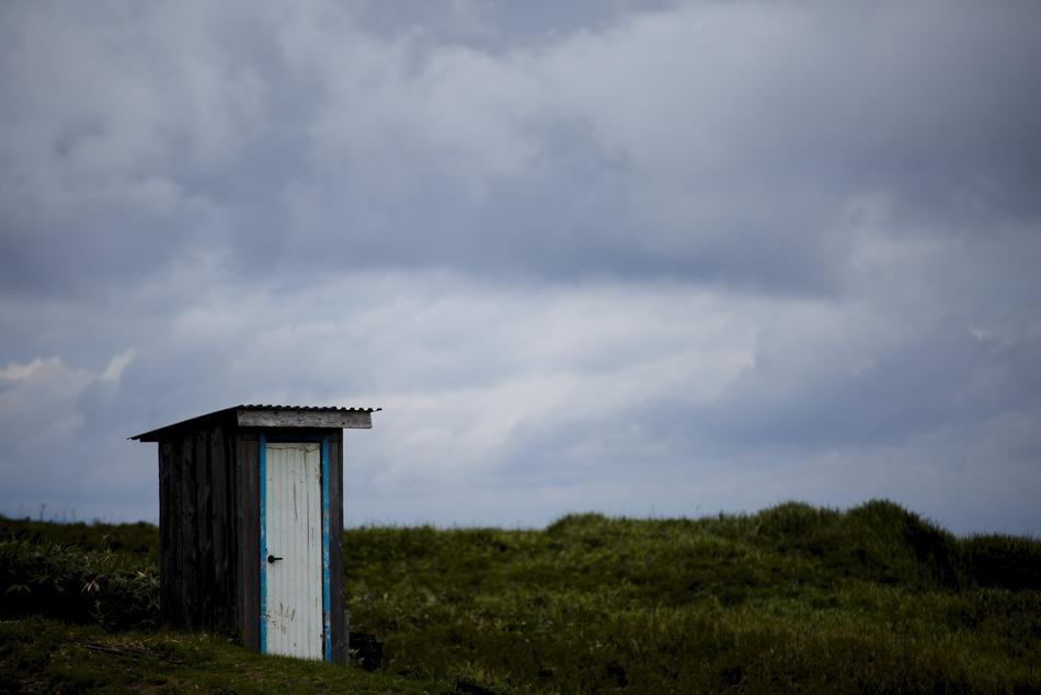 Inodoros Baños Publicos:Una caseta con un inodoro, en un campo de propiedad privada en el
