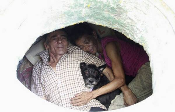 Restrepo looks up from his sewer home with his wife Maria Garcia in Medellin