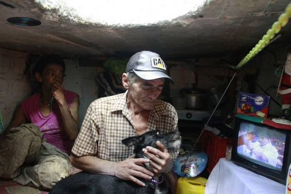 Restrepo plays with his dog Blackie in his sewer home in Medellin