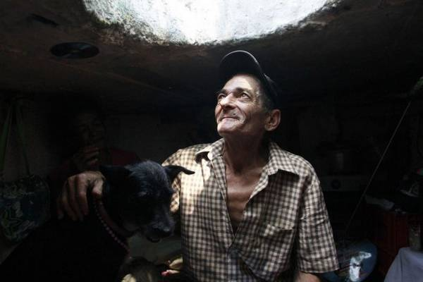 Restrepo looks up from his sewer home in Medellin