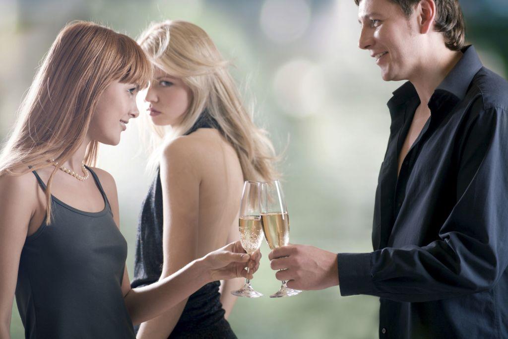 Una-mujer-joven-mirando-con-envidia-a-otra-mujer-que-esta-chocando-una-copa-y-hablando-con-un-hombre