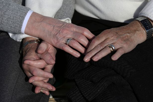 An-elderly-couple-hold-hands-as-they-sit-on-a-bench