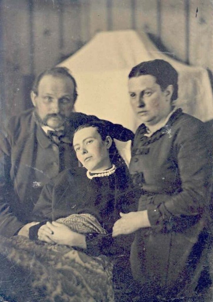 Victorian_era_post-mortem_family_portrait_of_parents_with_their_deceased_daughter-723x1024