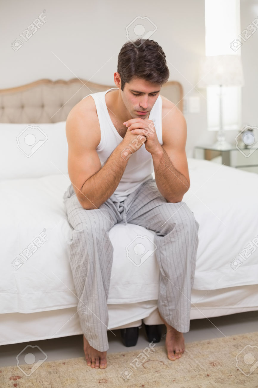 Full length of a thoughtful young man sitting in bed at home