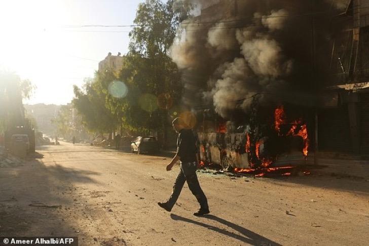 2lztk5efya1b9038a8ef275c7307-3815262-a_syrian_man_walks_past_a_bus_set_ablaze_following_a_reported_ai-a-30_1475232568860