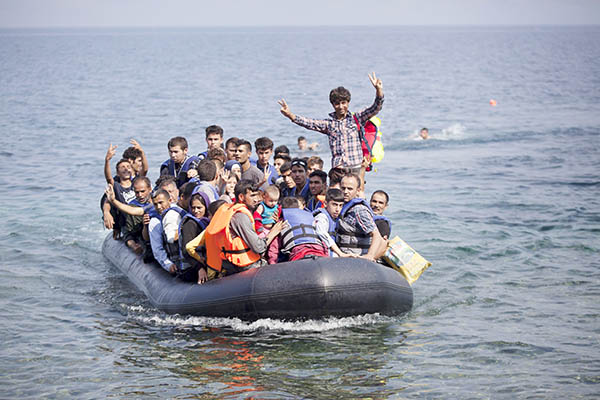 Syrian and Afghan refugees on a dinghy wave as they approach the Greek island of Lesbos