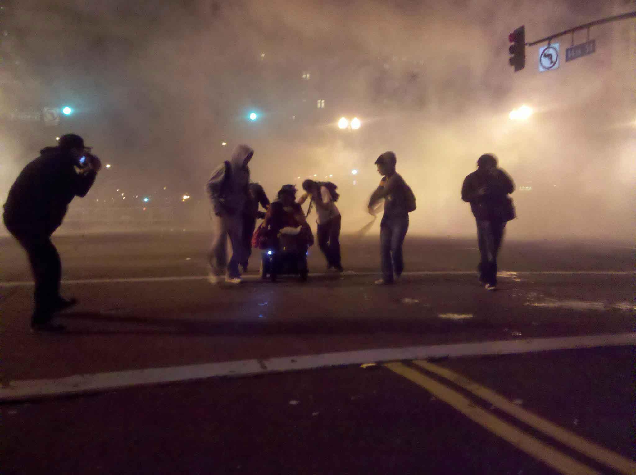 Manifestantes-ayudan-a-una-mujer-en-una-silla-de-ruedas-a-escapar-del-gas-lacrimógeno.-Oakland-EEUU-2011.