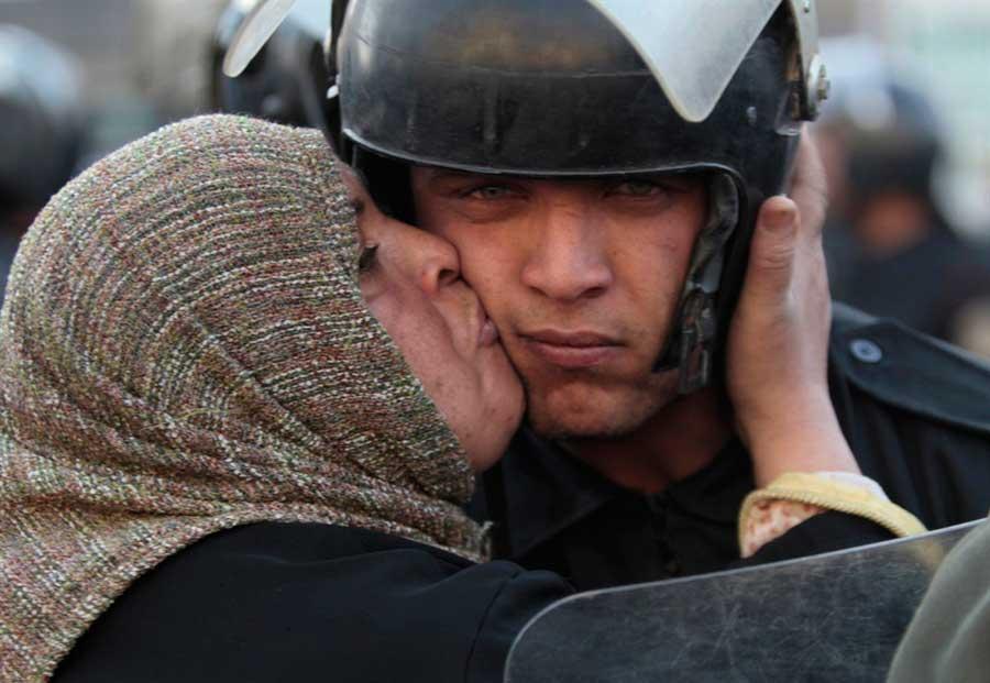 Mujer-egipcia-besa-a-un-policía-durante-la-revolución-del-gobierno-de-Mubarak.-Egipto-2011